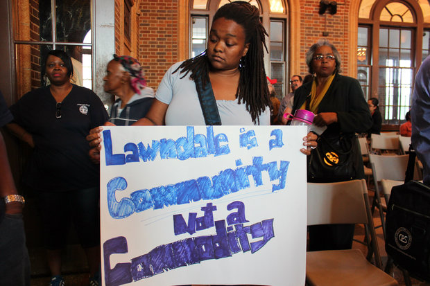 Sharaya Tindal, restorative justice coordinator at St. Agatha's Catholic Church, holds a sign protesting Riot Fest's move to Douglas Park at a community meeting Tuesday.