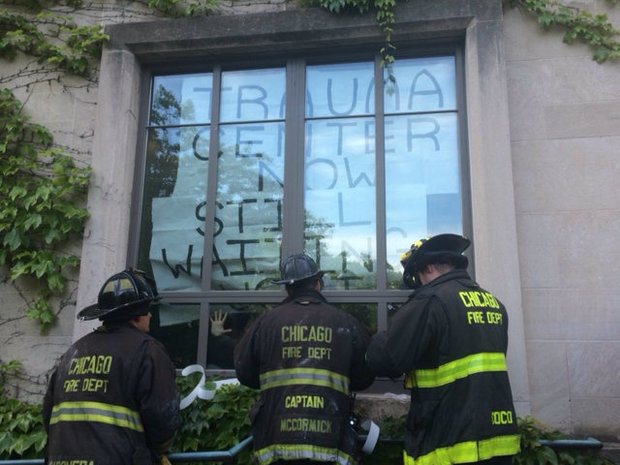 Chicago Fire officials prepare to break an exterior window of a University of Chicago administration building where protesters demanding a new trauma center had barricaded themselves in June.