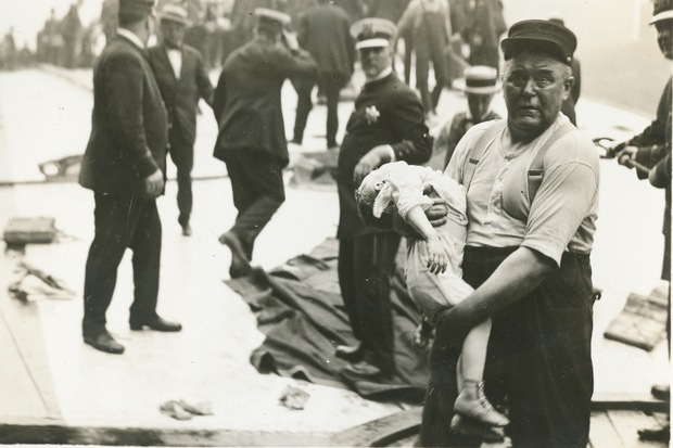 A firefighter cradles a dead infant in disbelief in recovering bodies from the Eastland disaster. The shot was taken by Jun Fujita, a photographer who worked for the Chicago Evening Post and later the Daily News.