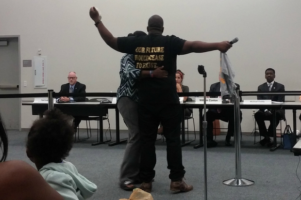 Martinez Sutton, brother of slain Rekia Boyd, holds up a bag that he said contained her bloody hair during a Police Board meeting. Boyd was shot and killed by a Chicago officer in 2012, and protesters called for the officer's firing during the meeting, which ended early after protesters took control of the crowd and began chanting.