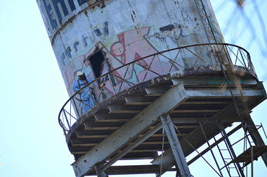 A worker can be seen along the Rosehill Cemetery water tower cat walk Wednesday with a blow torch.