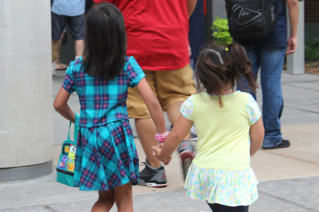 Kids hold hands on the first day of school in 2015.