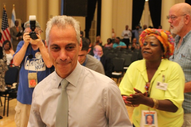 Mayor Rahm Emanuel arrives for Wednesday's budget forum at the South Shore Cultural Center. The woman behind him, Queen Sister, called him