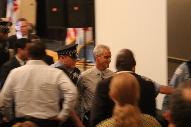 Police usher Mayor Rahm Emanuel out of Wednesday's public budget forum after Dyett protesters seized the stage.