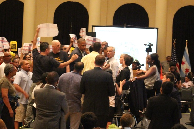 Dyett High School protesters rushed the stage at Wednesday's budget hearing, and in the end caused it to be shut down. Mayor Rahm Emanuel is at center.