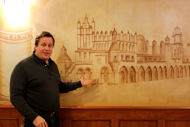 John Kapusciarz, general manager of The Mayor's Mansion, stands next to one of the many frescoes in his family's banquet hall.