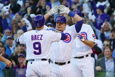 Javier Baez #9 of the Chicago Cubs is congratulated by Kyle Schwarber #12 of the Chicago Cubs after hitting a three-run home run in the second inning against the St. Louis Cardinals during game four of the National League Division Series at Wrigley Field on October 13, 2015 in Chicago.