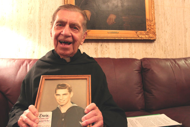 The Rev. Erwin Dodge displays a picture of himself from 1943. Dodge lives in the monastery at St. Rita High School in Ashburn. Dodge served in the Navy and was instrumental in having the memorial installed outside of the chapel at the all-boys Catholic high school.