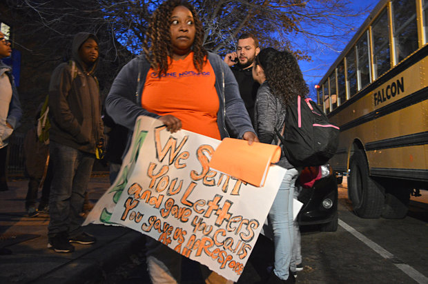 Ebony DeBerry, a ONE Northside organizer and parent of a student who gets on the bus at Eugene Field Elementary, holds a sign that refers to the struggle parents have faced getting attention from CPS.