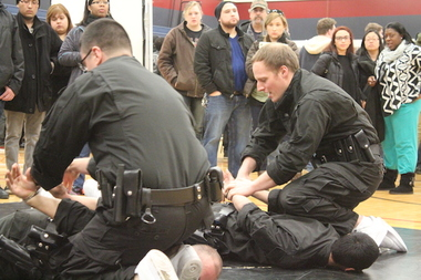 Police trainees stage mock arrests during an officer recruitment expo.