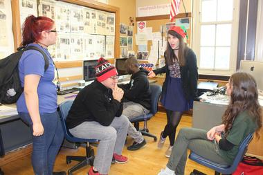 Reporter McKenzie Lacefield wears an elf hat while she discusses with her fellow editors and reporters how to proceed with the bell change story.