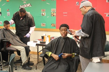 Jayvaughn Rice, 12, gets a free hair cut at the West Englewood Library. He is participating in the new Barbershop at the Library program, which brings together male teens and gets them talking about issues in their community.