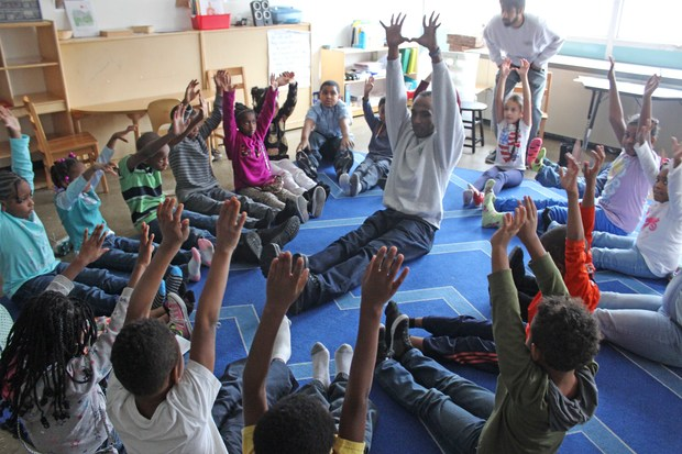 Students from the Montessori School of Englewood are learning yoga from I Grow Chicago volunteers.
