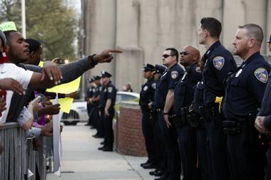 Baltimore Police Department officers stand behind a barrier while protestors gather near the Baltimore Police Department's Western District police station during a march and vigil over the death of Freddie Gray, April 21, 2015 in Baltimore, Maryland. Gray, 25, died from spinal injuries on April 19, one week after being taken into police custody.
