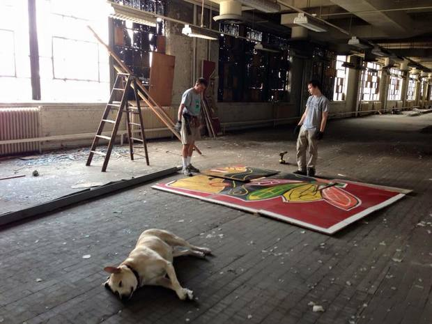 Painter Chris Toepfer with his son, William, inside the Old Main Post Office building with the Blackhawks mural he installed in 2010.