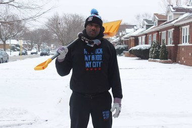 Jahmal Cole helps shovel snow on the 7900 block of S. Michigan Ave. Monday.