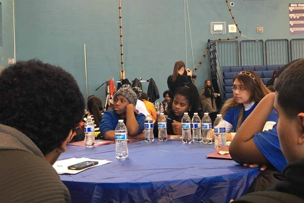 Elise Owens (l.), Jasaan'de Kemp (c.) and Aishah Peel listen to another student speak about the city's problems at a conference at Jones College Prep.