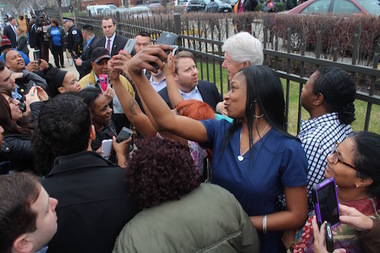 Clinton spent about a half hour shaking hands and taking pictures with a crowd of giddy local residents and employees of the nearby health center.