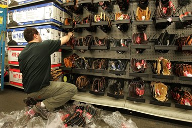 A man stocks baseball gloves at a Sports Authority store in suburban Niles in 2006.