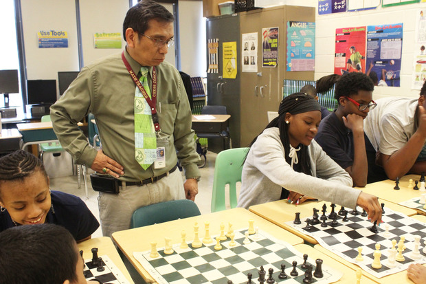 Earle STEM Academy chess coach Joseph Ocol helps his students practice after school.
