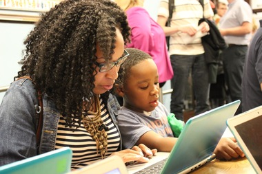 Tamara Anderson (l.) writes an email to legislators concerning the state's education budget as her son Zion, 6, looks on.