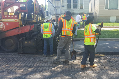 Department of Transportation workers repave the street in the 8300 block of South Kerfoot Avenue in Auburn Gresham on Monday. It's possible the material under the pavement is a