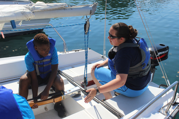 Shamar Thomas, 13, learns how to steer a sailboat with the help of Carpe Ventus mentor Laine Klopfenstein.