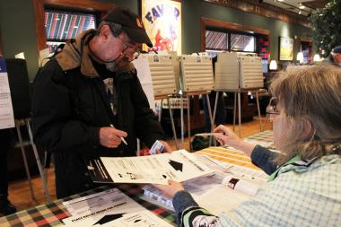A voter receives his ballot from an elections judge at Leona's Restaurant in Rogers Park on Nov. 6, 2012.
