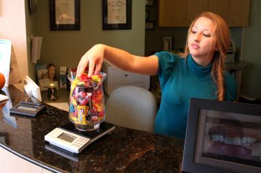 Belmont Dental Care secretary Janet Betancourt loaded candy on a scale to calculate the healthy donor's reward.