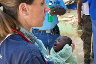 A volunteer for the International American Medical Mission organization holds a sick infant during a trip to Haiti in August.
