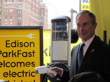 The mayor tests the city's first public electric car charging station.