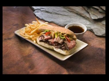 A Tri Tip sandwich with fries and au jus dipping sauce.