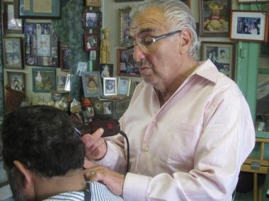 Claudio the Barber cuts a client's hair in his East Harlem storefront on Tuesday.