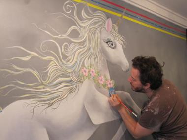 Artist Sam Simon touches up a portrait of Bea Arthur included in the unicorn mascot.