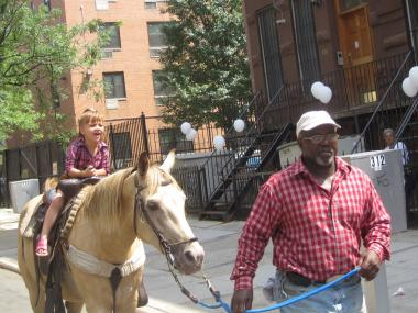 Frank McCall leads a child on a horse on 113th Street.