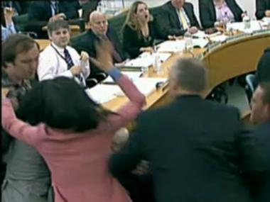 Wendi Deng Murdoch (in pink) rushed to her husband Rupert's side after a man tried to throw