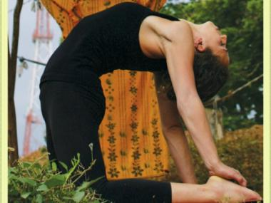 A woman does a back bend while practicing yoga.