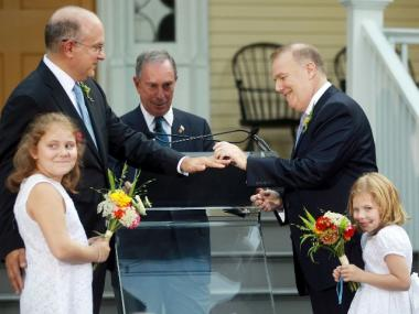 John Feinblatt and Jonathan Mintz exchange rings while marrying with their daughters Maeve and Georgia as New York Mayor Michael Bloomberg officiates at Gracie Mansion on July 24, 2011.