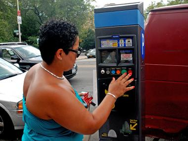 Mariana Tejada, 26, uses the Muni-Meter at Dyckman and Broadway on Aug. 1, 2011.