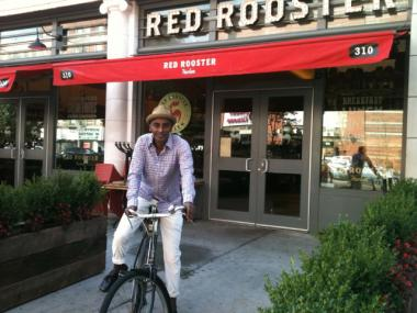 Marcus Samuelsson on a bike in front of his restaurant in Harlem. Samuelsson tweeted on July 26 that be would be bringing bikes to the eatery for patrons to borrow and explore the neighborhood.
