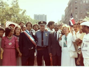 Miguel Amaro at the first Dominican Day Parade in 1982 (standing to the left of the police officer).  He was the founder of the event.