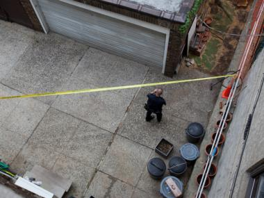Police investigate the crime scene in the rear courtyard of a two-story home on Park Terrace West.