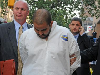 Officer Michael Pena (in white suit) was charged with raping a Bronx school teacher at gunpoint in Inwood on Aug. 19, 2011.