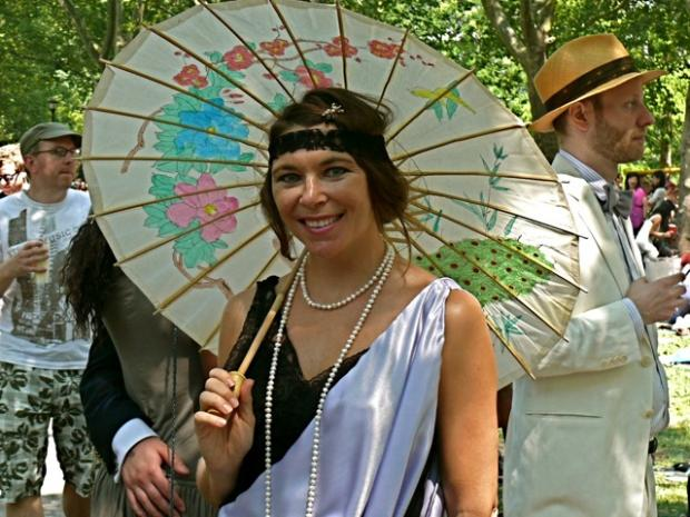 A black and white flapper inspired ensemble accessorized with a lace headband ropes of pearls and brightly colored floral parasol.