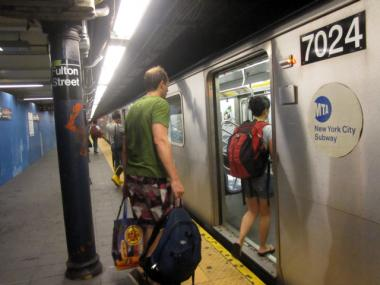 Straphangers board the train at the Fulton Street subway station.