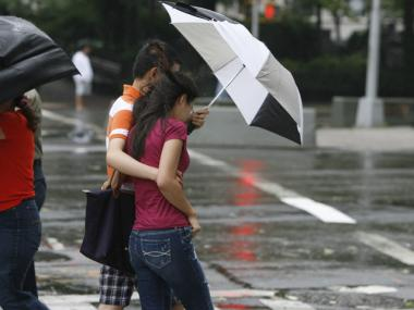 A couple walks together under an umbrella in Harlem during Hurricane Irene.