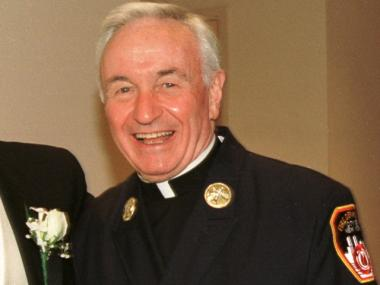 Fire Department chaplain Rev. Mychal Judge smiles for a photograph July 28, 2001.