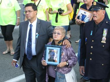 9/11 victims' family members hold photos of their loved ones at the 10th anniversary ceremony, Sept. 11, 2011.