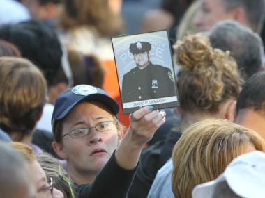 A relative holds up a photo of an NYPD officer at the 10th anniversary ceremony, Sept. 11, 2011.