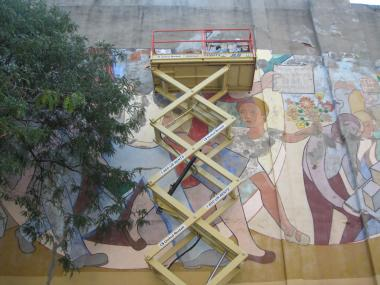 Experts inspect what needs to be done to restore a mural at Matthews-Palmer Playground in Hell's Kitchen.